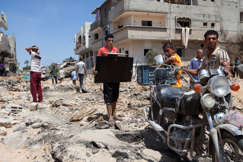Inhabitants of destroyed Kuza'a leave with their belongings.